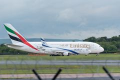 MANCHESTER UK, 30 MAY 2019: Emirates Airbus A380 flight EK18 to Dubai holds on a taxiway prior to takeoff with a much smaller. Boeing 737 from El Al Israel stock images