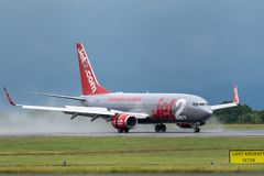 MANCHESTER UK, 30 MAY 2019: Jet2 Boeing 737 flight LS804 from Barcelona lands on runway 23R at Manchaester Airport with rainwater. Spraying up from the engines stock image