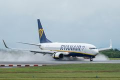 MANCHESTER UK, 30 MAY 2019: Ryanair Boeing 737 flight FR3217 from Milan lands on runway 23R at Manchaester Airport. Reverse engine. Thrust kicks up rain as royalty free stock photos