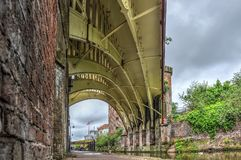 Manchester under the bridge. Under a historic steel railway bridge diagonally crossing the Rochdale canal in the Castlefield area in the center of Manchester Royalty Free Stock Photos