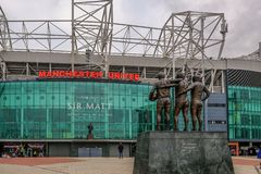 Manchester United Football stadium with statue of Best, Law and Charlton in the foreground