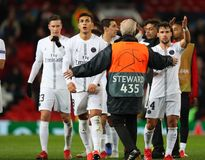 Manchester United v Paris Saint-Germain - UEFA Champions League Round of 16: First Leg. MANCHESTER, ENGLAND - FEBRUARY 12 2019: A steward stops PSG players from royalty free stock image