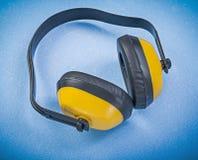 Manchons d'oreille de sécurité sur le concept bleu de construction de fond Photos libres de droits