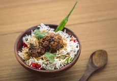 Manchurian with cooked rice in a bowl. Homemade manchurian and cooked rice with sauces in a wooden background Royalty Free Stock Photos