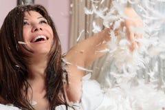 Manciata di lancio della donna di divertimento di piuma e giù fotografia stock libera da diritti