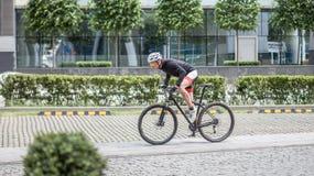Mancyklist i sportswearritt på vägen i staden royaltyfri foto