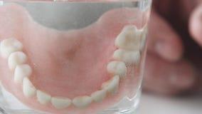 Mandíbula desprendible en un vidrio, primer La mano de un hombre pone los dientes falsos en un vidrio de la solución Cuidado dent metrajes