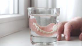 Mandíbula desprendible en un vidrio, primer La mano de un hombre pone los dientes falsos en un vidrio de la solución Cuidado dent almacen de metraje de vídeo