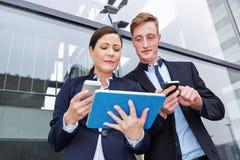 Mand et femme comparant le smartphone Photo libre de droits