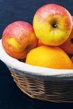 Mand met appelen en sinaasappelen op een blauwe achtergrond Stock Foto