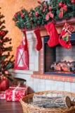 Mand met brandhout dichtbij de Kerstmisopen haard Stock Foto's