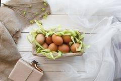 Mand met eieren en de lentedecor op een witte houten achtergrond Stock Foto
