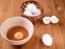 Mand met eieren, houten kom met dooier op een houten lijst Stock Foto