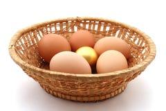 Mand met gebruikelijk kippenei en gouden ei stock foto's