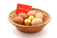 Mand met gebruikelijk kippenei en gouden ei stock afbeelding