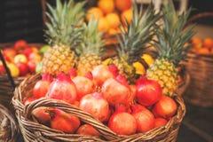 Mand met granaatappel en ananas Stock Foto