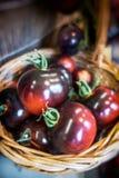 Mand met organische bruine kumatotomaten bij de keuken Stock Foto
