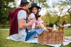 Mand met voedsel en dranken die zich dichtbij paar in park bevinden stock fotografie