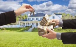 Mand que entrega o dinheiro da mulher para chaves na frente da casa Imagens de Stock