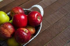 Mand in rode appelen, mandhoogtepunt van appelen, appelenbeelden op authentieke houten vloer, Stock Foto's