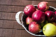 Mand in rode appelen, mandhoogtepunt van appelen, appelenbeelden op authentieke houten vloer, Stock Afbeelding