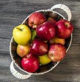 Mand in rode appelen, mandhoogtepunt van appelen, appelenbeelden op authentieke houten vloer, Royalty-vrije Stock Afbeeldingen