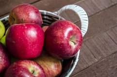 Mand in rode appelen, mandhoogtepunt van appelen, appelenbeelden op authentieke houten vloer, Stock Fotografie