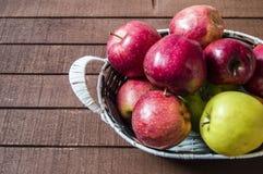 Mand in rode appelen, mandhoogtepunt van appelen, appelenbeelden op authentieke houten vloer, Royalty-vrije Stock Afbeelding