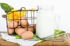 Mand van bruine eieren en waterkruik melk Royalty-vrije Stock Afbeeldingen