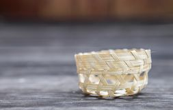 Mand van het close-up de kleine met de hand gemaakte bamboe op houten vloer Stock Afbeeldingen
