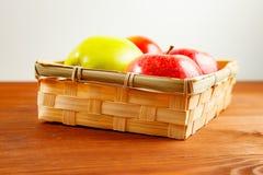 Mand van verse rijpe rode appelen op houten achtergrond stock afbeeldingen