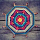 Mandala tibétain tricoté des fils sur le fond en bois images stock