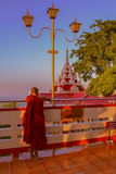 MANDALAY, BURMA - NOVEMBER 12, 2014: Monk on Mandalay hill. Monk watching the sunset with ponoramnoy site on a hill Royalty Free Stock Photography