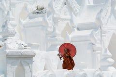 Mandalay, Myanmar - April 2019: Buddhist novice monk with red umbrella walking on the walls of Myatheindan Pagoda stock photo