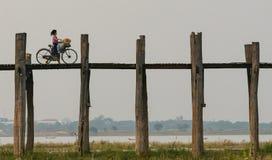Mandalay, Myanmar 22-April-2018 Señora joven que cruza el puente de U Bein con una bicicleta en la región de Mandalay imagen de archivo