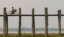 Mandalay, Myanmar. 22-April-2018. Young lady crossing U Bein Bridge with a bicycle in Mandalay region stock image