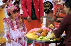 MANDALAY, MYANMAR - 18 DICEMBRE 2015: Ragazza birmana sveglia che sceglie frutti durante la cerimonia a Maha Muni Pagoda immagine stock libera da diritti
