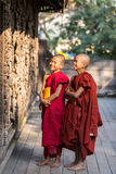 MANDALAY,MYANMAR-FEB 18 : Young Novice monks standing and looking at Shwenandaw Monastery is built in the traditional Burmese arc. Hitectural style on February 8 stock photos