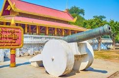 The guard of the Royal Palace in Mandalay, Myanmar. MANDALAY, MYANMAR - FEBRUARY 23, 2018: The cannon on the stone basement guard the entrance to the Royal royalty free stock photos