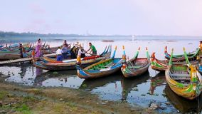 Boats in harbor of Thaungthaman lake, Mandalay, Myanmar. MANDALAY, MYANMAR - FEBRUARY 21, 2018: The small harbor on Taungthaman Lake with numerous colored boats stock footage