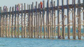 MANDALAY, MYANMAR - 13 JAN 2014: U Bein Bridge across the Taungthaman Lake. The 1.2 km  bridge was built around 1850 and is the ol stock video footage