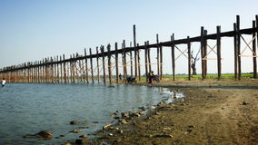 MANDALAY, MYANMAR - 13 JAN 2014: U-Bein Bridge across the Taungthaman Lake. The 1.2 km  bridge was built around 1850 and is the ol stock video