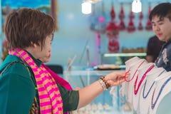 MANDALAY-Myanmar Januari 20, 2019: Oidentifierade turister väljer att köpa smycken från gemstones på smycken shoppar på januari 2 arkivfoto