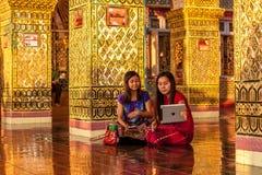 MANDALAY, MYANMAR - Nov 26, 2014: Two Myanmar. MANDALAY, MYANMAR - Nov 26, 2014: Two Myanmar girls taking selfie on ipad in the temple at Mandalay Hill royalty free stock photos