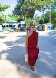 MANDALAY, MYANMAR - November 17, 2015: Young monk with his alms Royalty Free Stock Photos