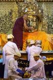 The ritual of daily face washing Mahamuni Buddha at Mahamuni pagoda in Mandalay, Myanmar. Stock Photos