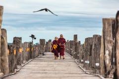 Unidentified novices walking on U Bein Bridge near Mandalay in Myanmar. Royalty Free Stock Photography