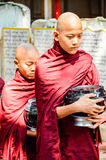 MANDALAY, MYANMAR- SEPTEMBER 26, 2016: Buddhist monks collecting alms at the temple Royalty Free Stock Image