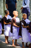 MANDALAY, MYANMAR- SEPTEMBER 26, 2016: Buddhist monks collecting alms at the temple Royalty Free Stock Photography
