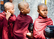 MANDALAY, MYANMAR- SEPTEMBER 26, 2016: Buddhist monks collecting alms at the temple Royalty Free Stock Photos